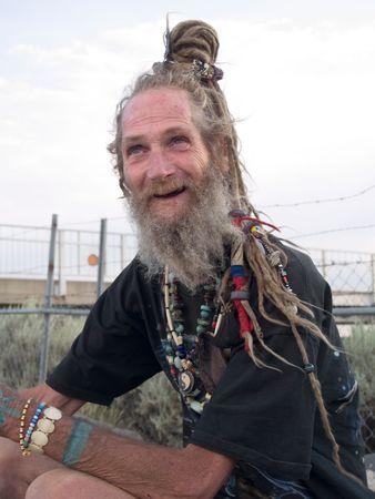 Happy older gentleman with his dreadlocks on a bun