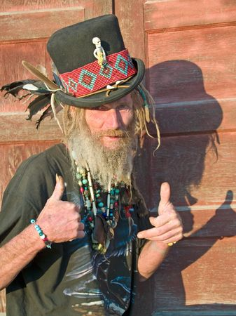 man's thumb: Eccentric older gentleman with dreadlocks and a top hat thumbs up Stock Photo