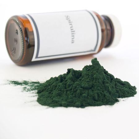 algen: Spirulina fles en geïsoleerd op wit poeder. Het generieke etiket werd gemaakt voor de fotoshoot, geen overtredingen.