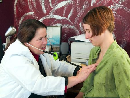stethoscope: Female doctor listening to young patient's heart