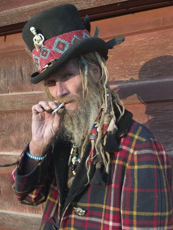 An eccentric older gentleman with dreadlocks and a top hat smoking rolling tobacco