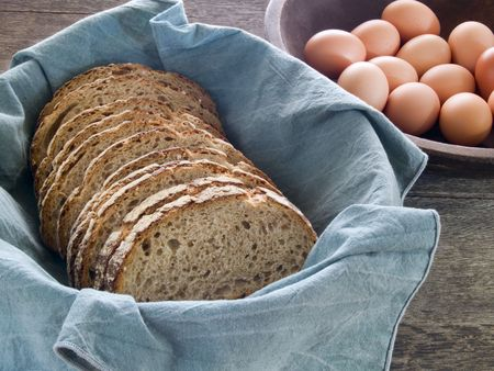 Fresh whole wheat bread in a basket with brown eggs in the background on a rustic wooden table