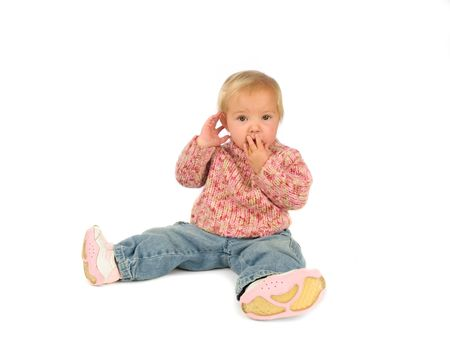 covering: Speak no evil, hear no evil. Little girl in pink pullover and blue jeans. Stock Photo
