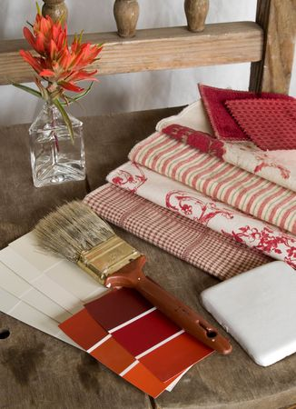 Red and white color cards, fabric swatches and a white ceramic tile on an old, rustic, unpainted chair with a paintbrush and red flowers. Фото со стока