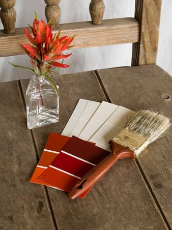 Red and white paint project - an old chair in need of a rejuvenation. Red and white paint sample cards and a paintbrush with red flowers on an old unpainted chair. Stock Photo
