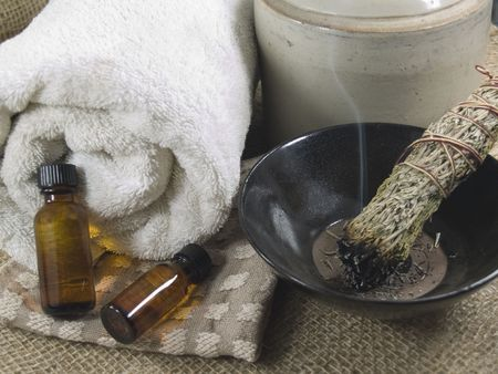 smudge: Two bottles of massage or aromatherapy oil on a washcloth, white cotton towel and a smudge stick burning. Stock Photo