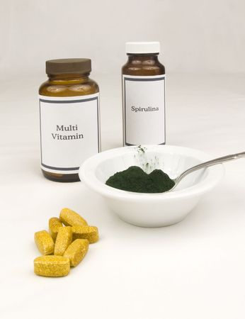 Multi vitamin and spirulina bottles with spirulina powder and vitamin tablets.  Stock Photo