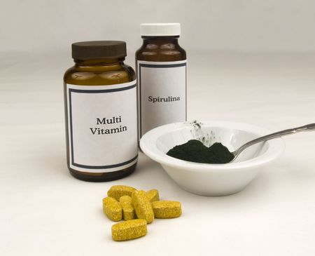Multi vitamin and spirulina bottles with spirulina powder and vitamin tablets.  photo