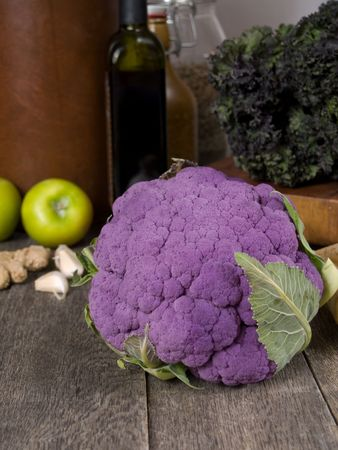 cruciferous: Purple cauliflower on a rustic kitchen table with chard, apples, garlic, ginger and storage bootles in the background
