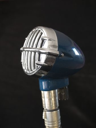jazz time: A vintage blue microphone on a black background.