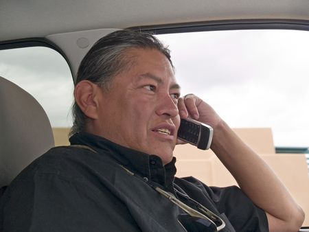 Native American man talking on cell phone in his parked car.