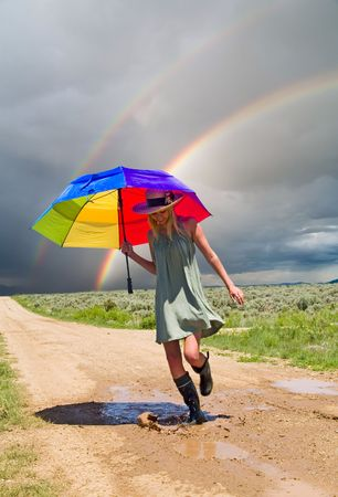 umbrella rain: Girl splashing water in a puddle after a rain