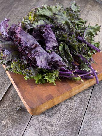 Repollo: Kale rojo en una tabla para cortar madera  Foto de archivo