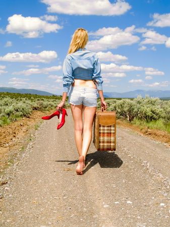 Girl walking on a dirt road barefoot with a suitcase carrying her red shoes