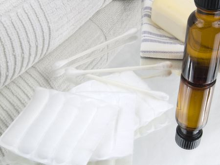 swaps: A white cotton towel with a bottle of cleansing alcohol soap wash cloth cotton squares and swaps.