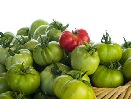 Green tomatoes and with one red in a basket isolated on white background.