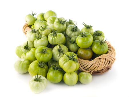 Green tomatoes in a basket isolated on white background.