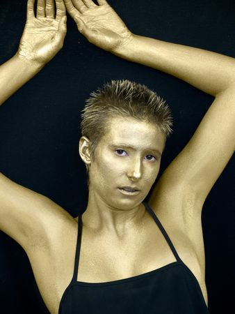 Golden androgynous woman on a black background
