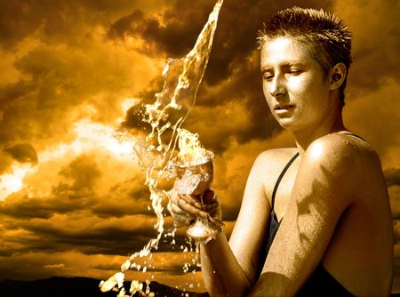 Water Goddess - young woman holding holding a cup under pouring water against stormy skies. Stock Photo - 6121427