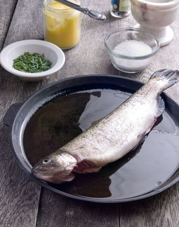greased: Freshly caught trout in a greased cast iron pan on a rustic table with sea salt, butter and chives.