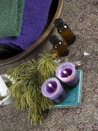Crystal wand with candles and aromatherapy or massage oil bottles photo