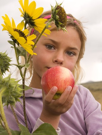 Little girl holding or offering an apple  photo