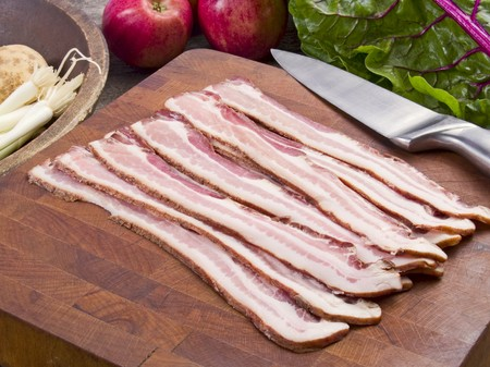 uncooked bacon: Uncooked bacon on a cutting board with a knife surrounded by vegetables and apples on a rustic kitchen table