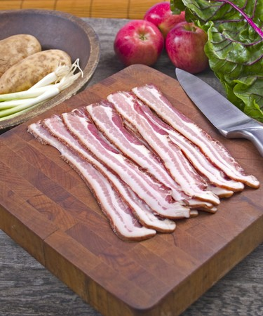 uncooked bacon: Uncooked bacon on a cutting board with a knife surrounded by chard, scallions, potatoes and apples on a rustic kitchen table