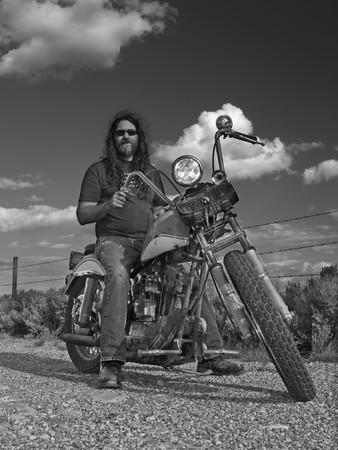 Langharige fietser op een oude klassieke, gedeeltelijk zelfgebouwde, Amerikaanse motorfiets
