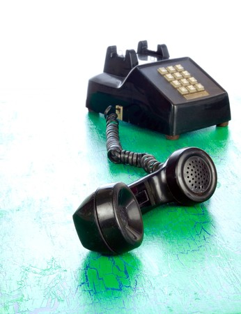 Grunge bush button phone from around 1970 on cracking and peeling green surface Stock Photo - 7316922