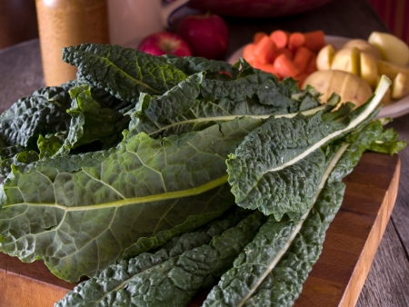 Lacinato kale on a wooden cutting board with other vegetables in the background