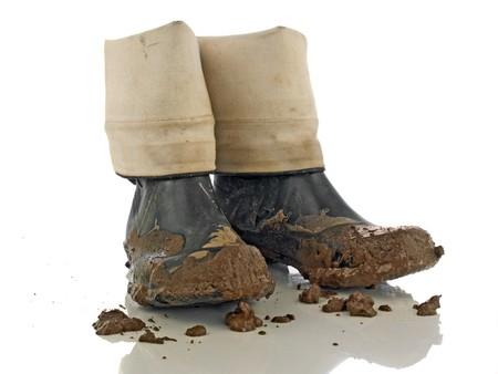 Muddy rubber laarzen op witte reflecterend oppervlak Stockfoto