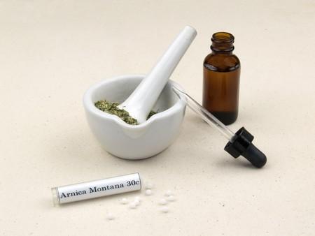 Natuurlijk medicijn. Pipet fles tinctuur, kruiden in een vijzel en een tube Arnica Montana homeopathie.