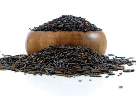Wild rice in a wooden bowl isolated on white background