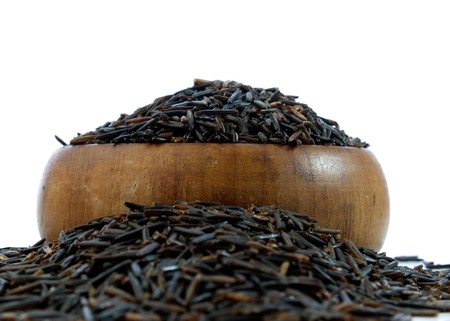 Wild rice in a wooden bowl isolated on a white background