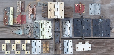 Weathered old hinges to be recycled and reused displayed on old rustic wood Stok Fotoğraf