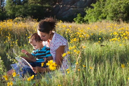 Mother and son reading a book together in late afternoon sun