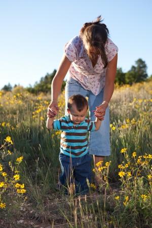 Avondwandeloefening - babyjongen die leert lopen. Ondiepe DOF, focus ligt op het gezicht van de jongen.