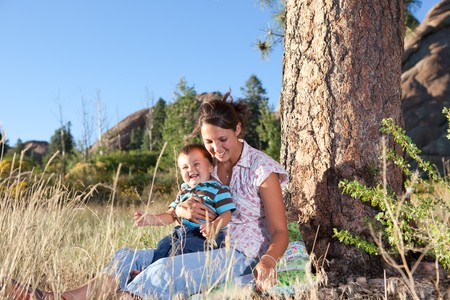 Mother and son goofing under a big pine tree in afternoon sun Stock Photo - 7766434
