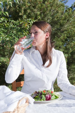Young woman drinking water and eating a healthy salad outdoors on a restaurant patio photo