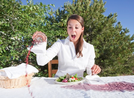 Woman spilling wine - trying to pick the glass and making things just worse