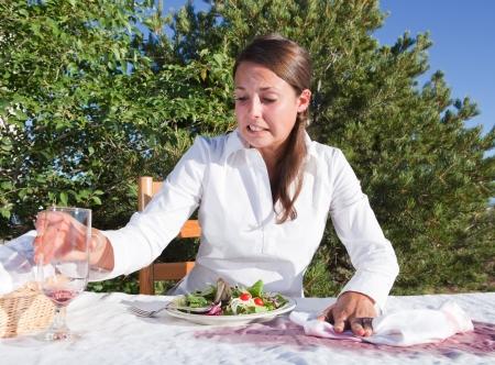 Beschaamd jonge vrouw probeert te schoon na het morsen van wijn op witte tafel laken