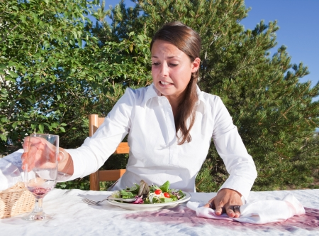 Embarrassed young woman trying to clean after spilling wine on white table cloth photo
