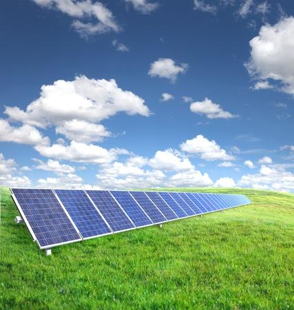 Zonne panelen op groen gras met blauwe hemel