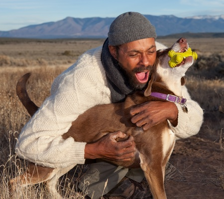 Man playing with his dog. Goofing, petting and howling. Stock Photo