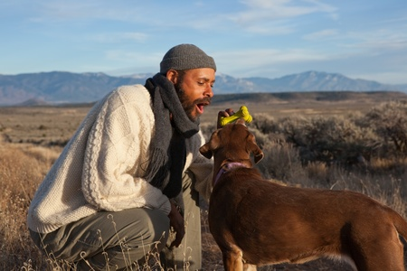 Casual African American man playing with and talking to his dog