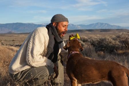 Casual African American man spelen met en praten met zijn hond  Stockfoto