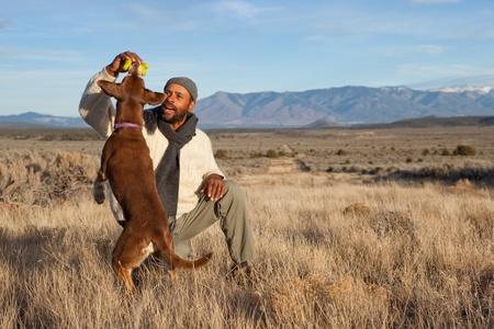 perros jugando: Casual hombre afroamericano, jugando con su perro al aire libre Foto de archivo