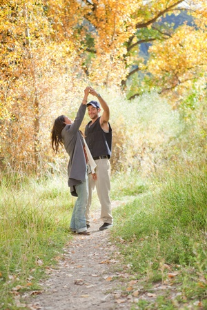 Young couple dancing in colorful autumn forest 스톡 콘텐츠