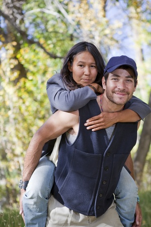 Young multi ethnic couple in autumn forest. Shallow DOF, focus is on the girls face.